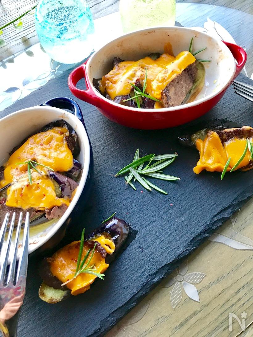 黒いお皿に盛られたなすと牛タンのミモレットチーズ焼き