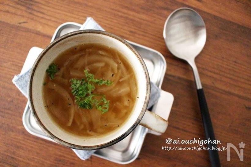 オニオンスープを注いだカップとスプーン