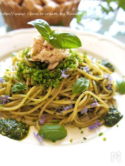 バジルオイルのからまったスパゲッティの上に刻んだチャイブとツナ、生バジルをのせて