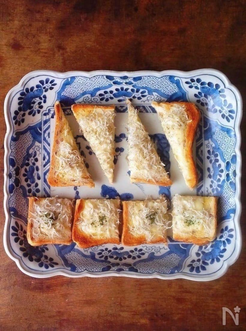 青の皿に盛られた三角にカットされたしらすのチーズトースト