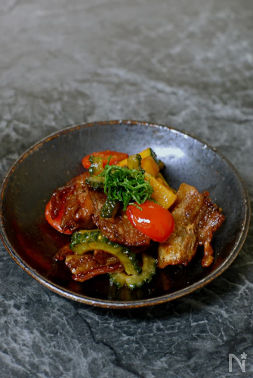 黒の小鉢に盛られたゴーヤやトマトの炒め物