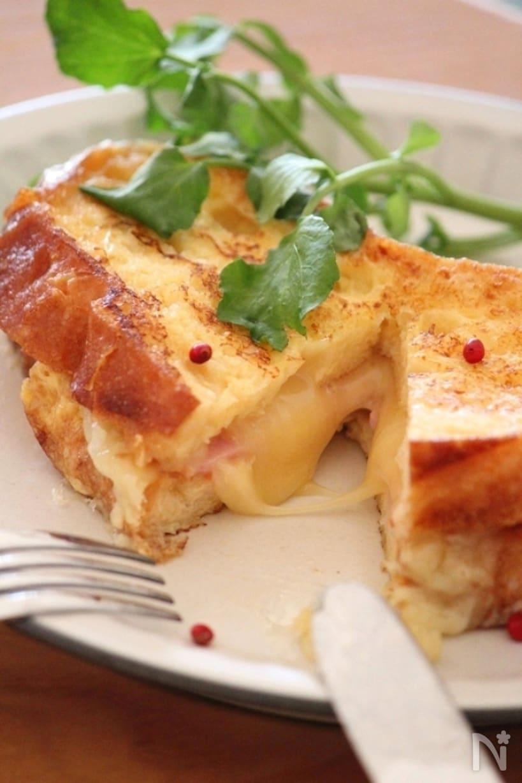 ハムチーズをはさんだフレンチトーストを半分に切っている画像