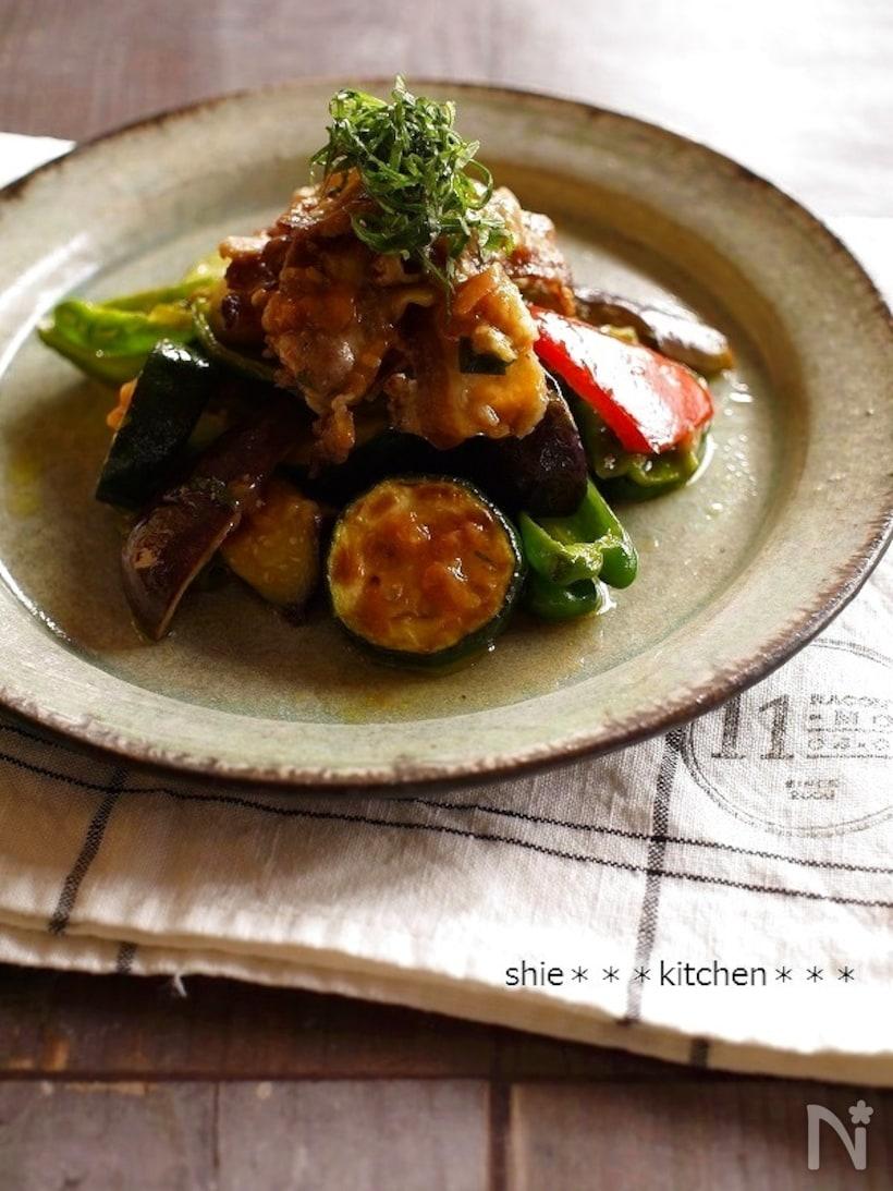 ベージュの和皿に盛られた豚肉となすとズッキーニとパプリカとピーマンの梅しそオリーブ和え