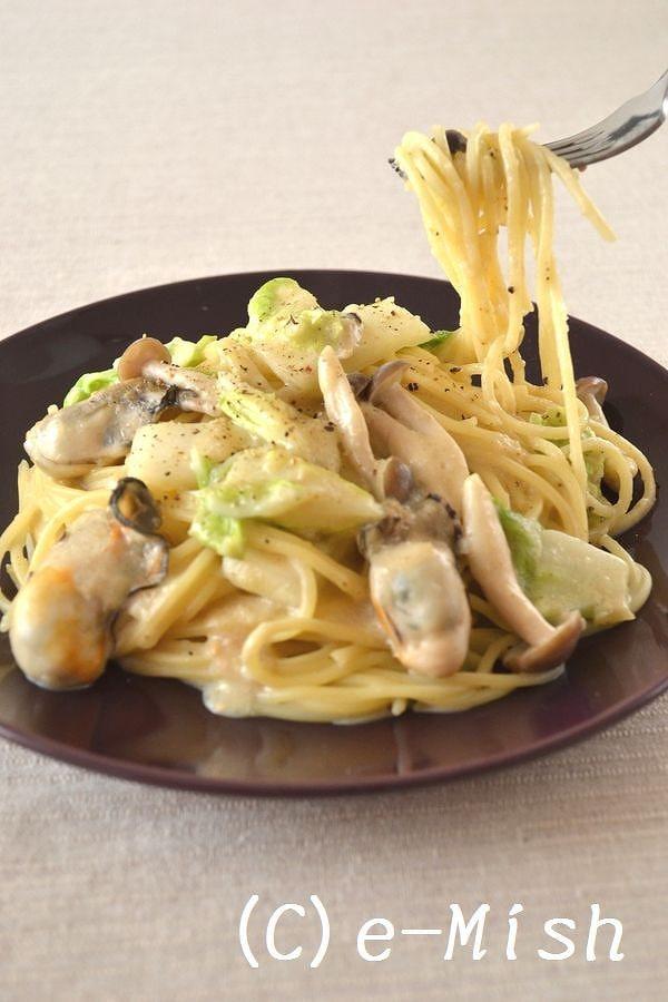 黒の皿に盛られたかきと白菜のクリームパスタ