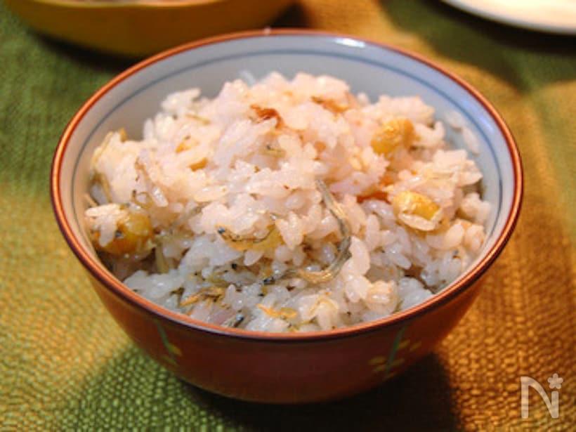 テーブルの上、お茶碗によそわれた蒸し大豆入りの梅干しじゃこご飯