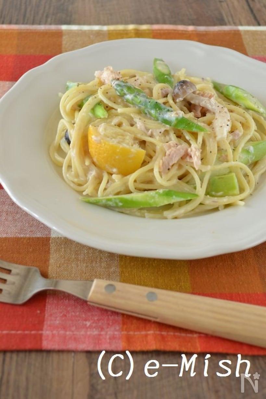 暖色ギンガムチェックのランチョンマットに置かれたフォークと白く丸い皿に盛られたアスパラとツナの塩レモンクリームパスタ