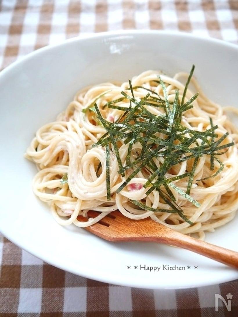 白いお皿に盛られたツナと梅のクリームパスタと、添えられた木製のフォーク