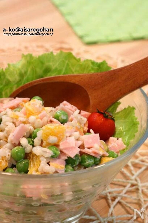 ガラス製の器に盛り付けられた押し麦、えんどう豆、ハムの入ったサラダ