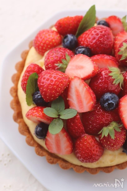 イチゴとブルーベリーが盛りだくさんのタルトケーキを上から撮影した画像