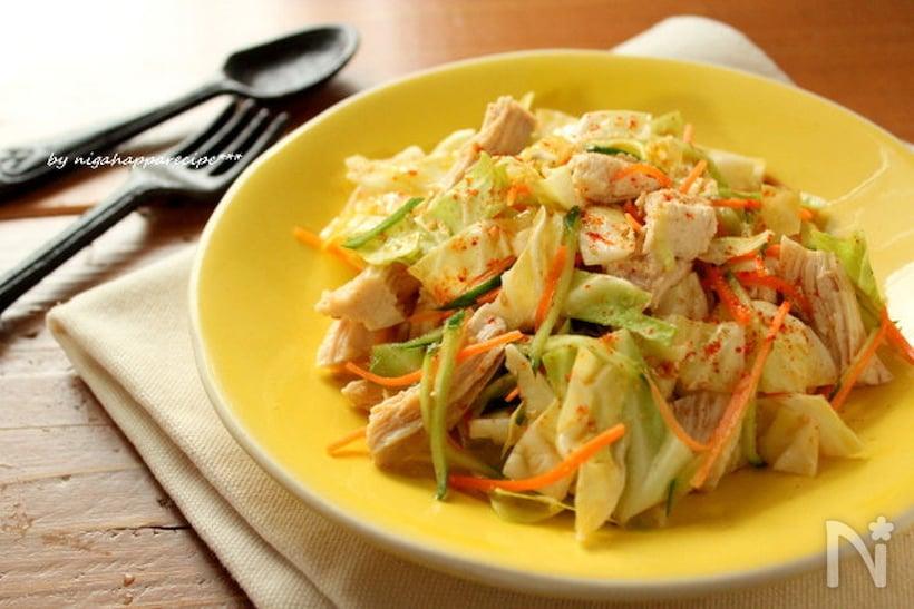黄色い皿に盛られている、蒸し鶏とキャベツ和えサラダ
