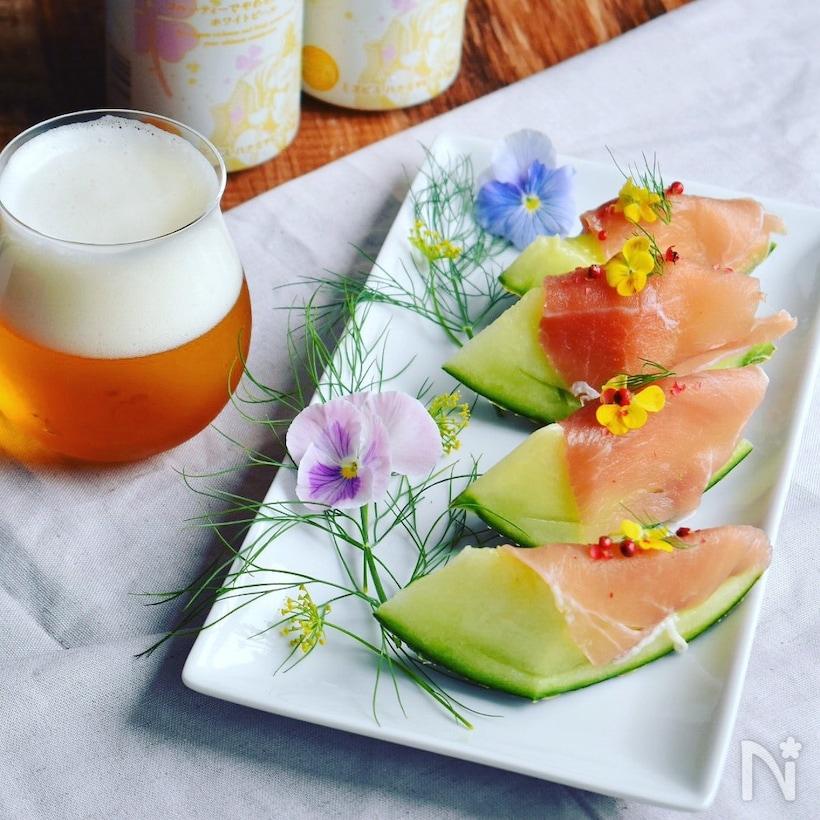 エディブルフラワーやハーブと白い皿に盛られた生ハムメロン