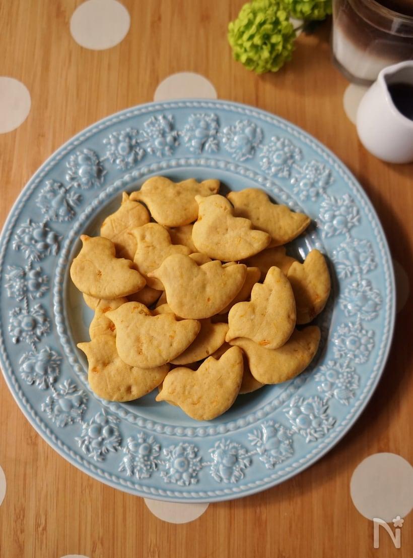 フチに模様の入った青い平皿に盛られたアヒル形のクッキー