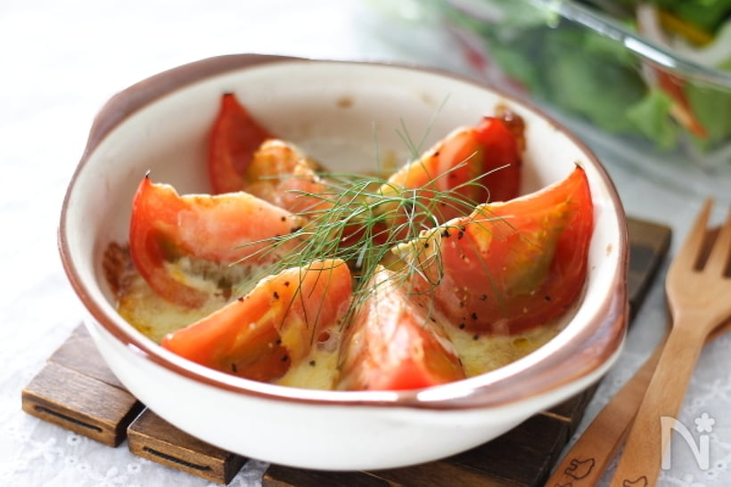 白いグラタン皿に盛り付けられたフェンネルののったトマトのチーズ焼き