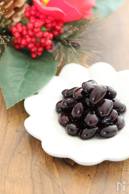 白い皿に光る黒豆が盛り付けられている画像