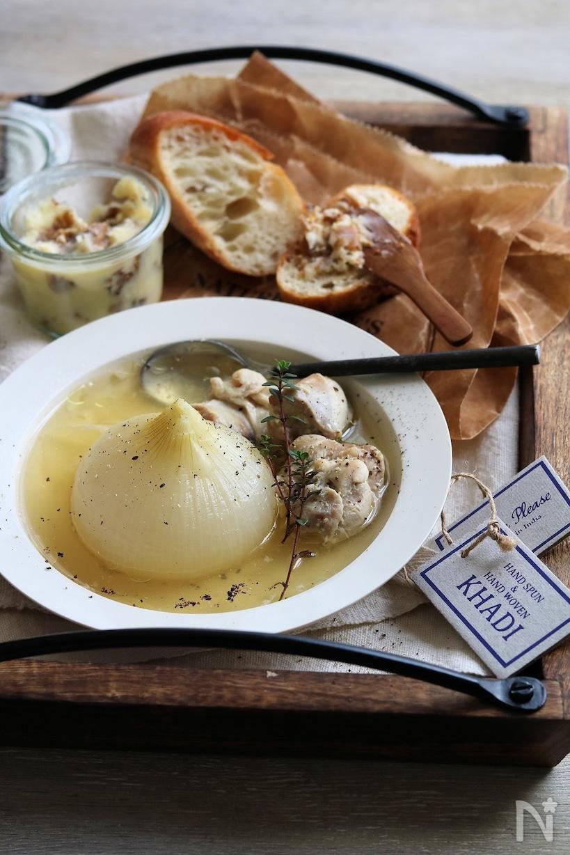 パンと白い皿に盛りつけた新玉ねぎのチキンスープ