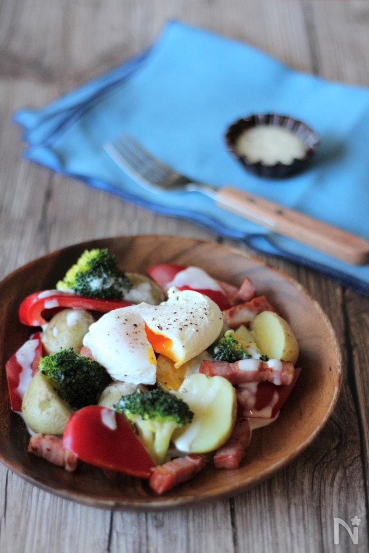 木皿に盛り付けたポーチドエッグのせ温野菜、水色のクロスとフォーク