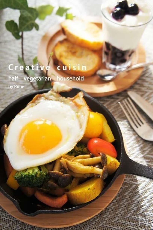 スキレットに盛り付けたカレー風味温野菜と目玉焼き、木皿に盛り付けたパンとグラスヨーグルト