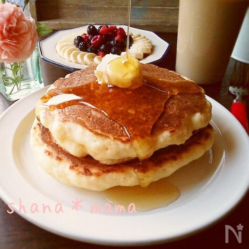 シロップをかけているパンケーキと、フルーツの盛り合わせとカフェオレ