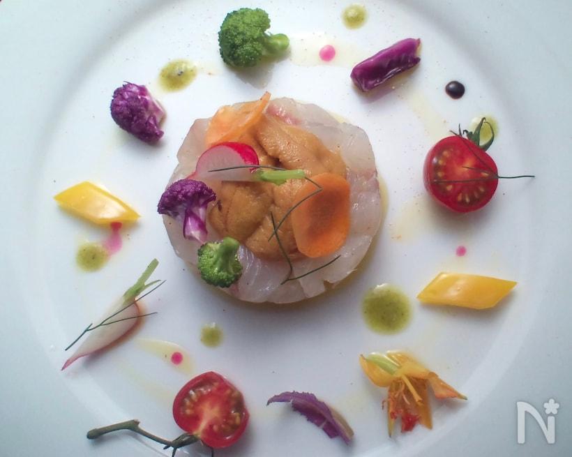 白い皿に、野菜とともにおしゃれに盛られた白身魚のカルパッチョ