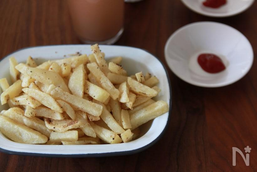 白い角ボウルに盛り付けられたフレンチフライと、ケチャップがのった豆皿。