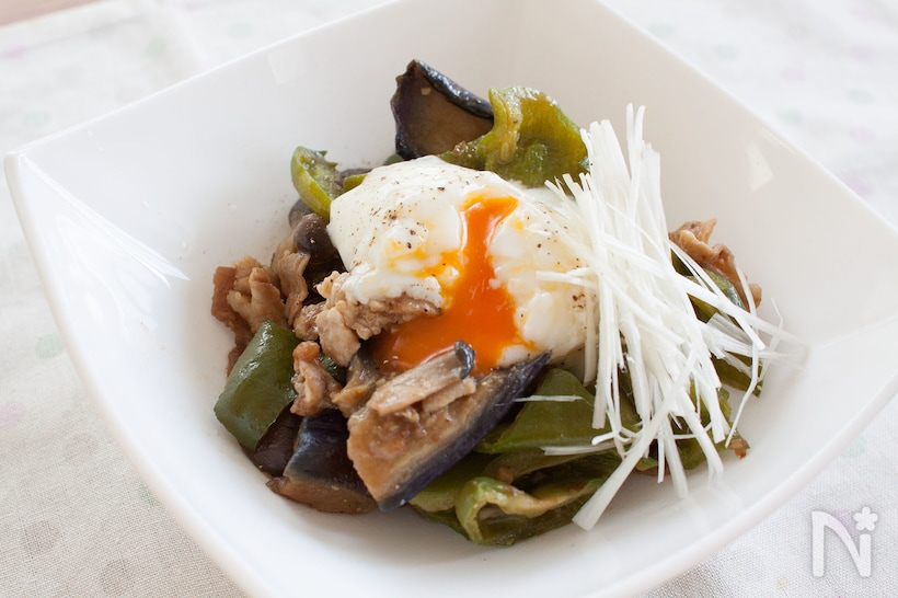 半熟卵と白髪ねぎをトッピングした豚肉、ピーマン、なすの味噌炒め
