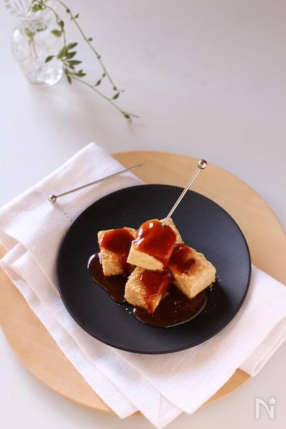 木製トレイと黒いお皿に盛られた、ピックの添えられたわらび餅