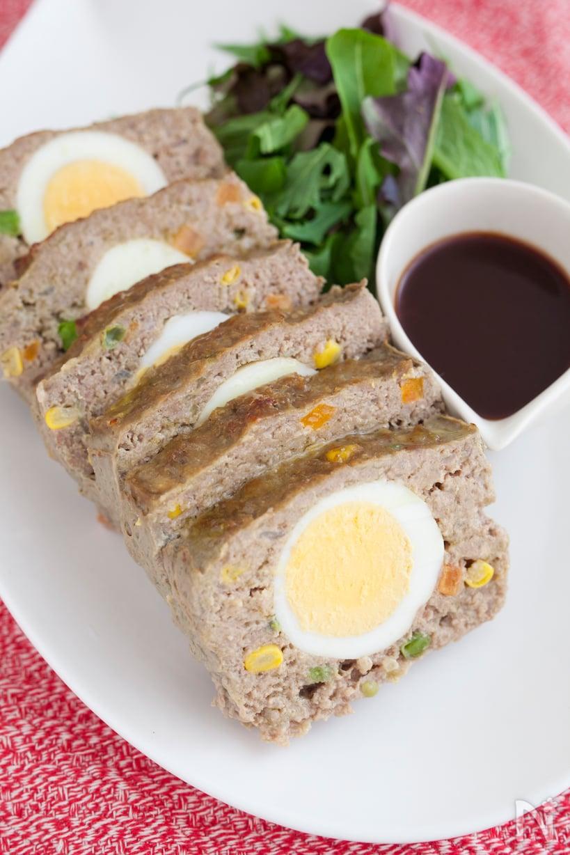 白の皿に盛られ、ゆで卵が入ったミートローフ