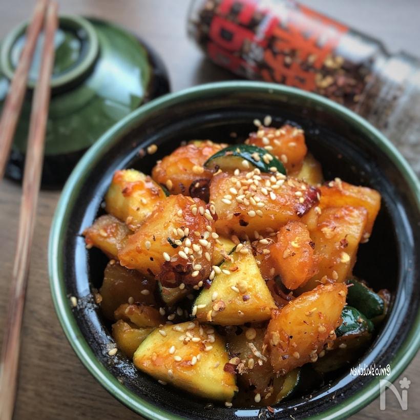 黒緑色の丸皿に盛り付けられた、ズッキーニとじゃが芋の韓国風炒め