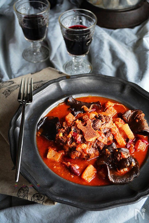 黒いお皿にワインとともに置かれた牛テールとセロリのトマト煮込み