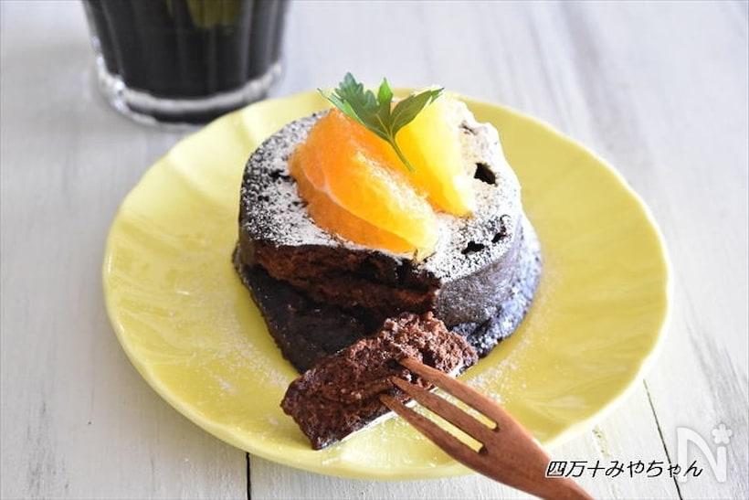 オレンジがのった円型のチョコレートケーキとフォーク