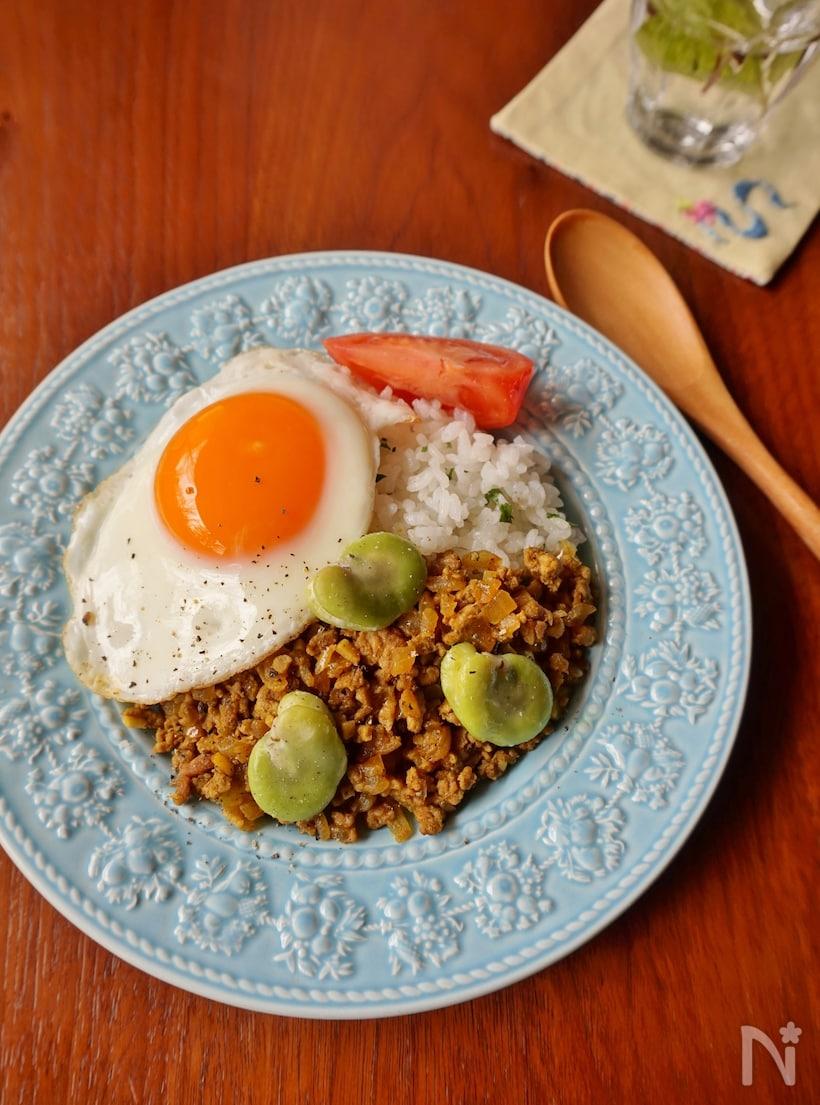 水色平皿に盛られたご飯とそら豆ドライカレーの上にのった目玉焼き