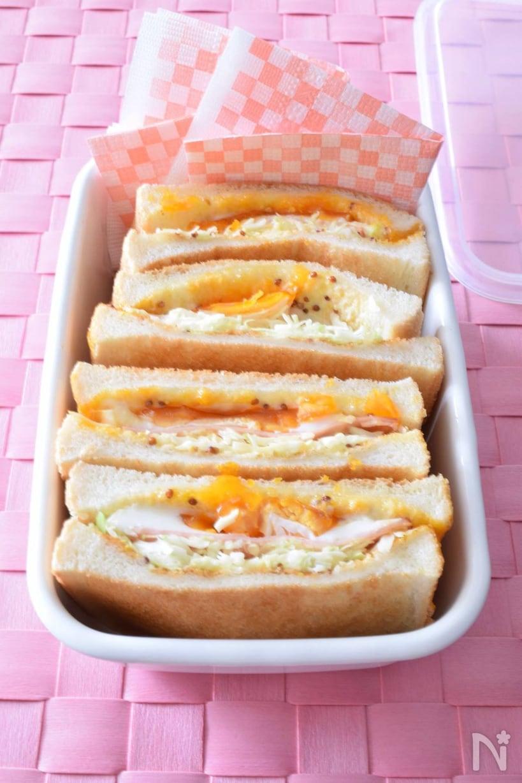 ピンクのランチョンマットの上に容器に入れて置いたハムエッグトーストサンド