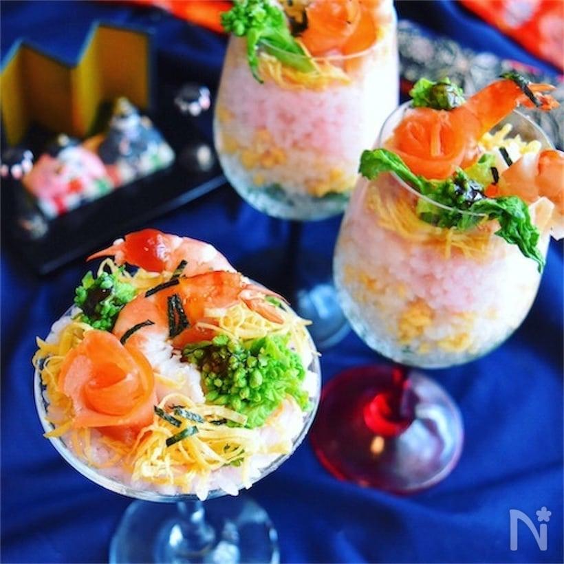 サーモン、菜の花、錦糸卵、海老をトッピングした寿司の入ったカクテルグラス
