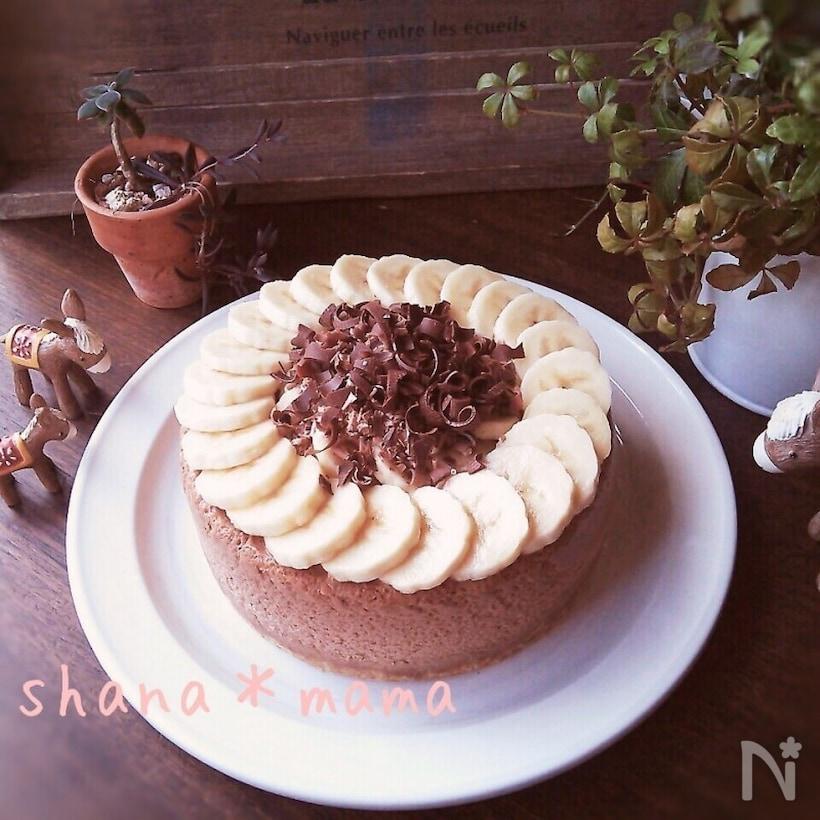 バナナの輪切りと削ったチョコが飾られたチョコのホールケーキ