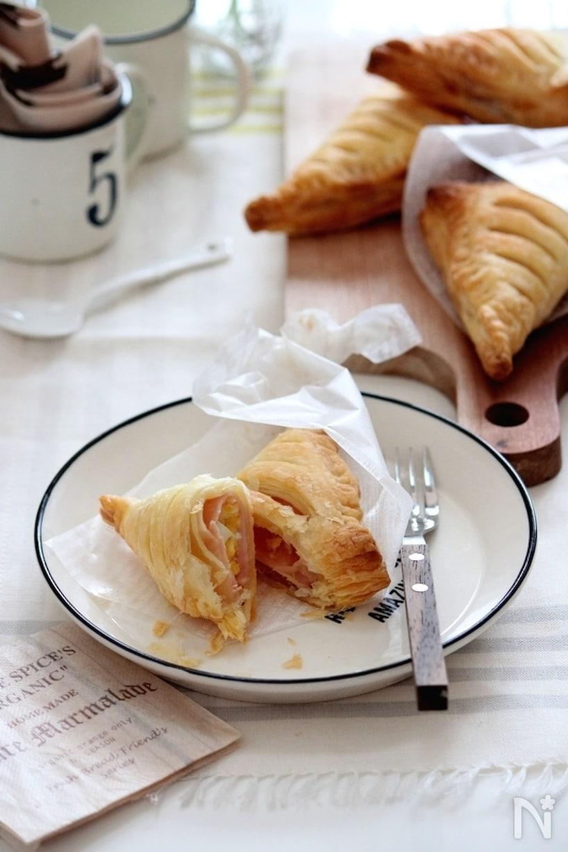 フチに紺のラインが入った白い皿に盛られたハムたまごパイとフォーク