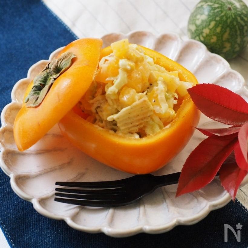 柿を器にしたサラダに黒のフォークが添えてある