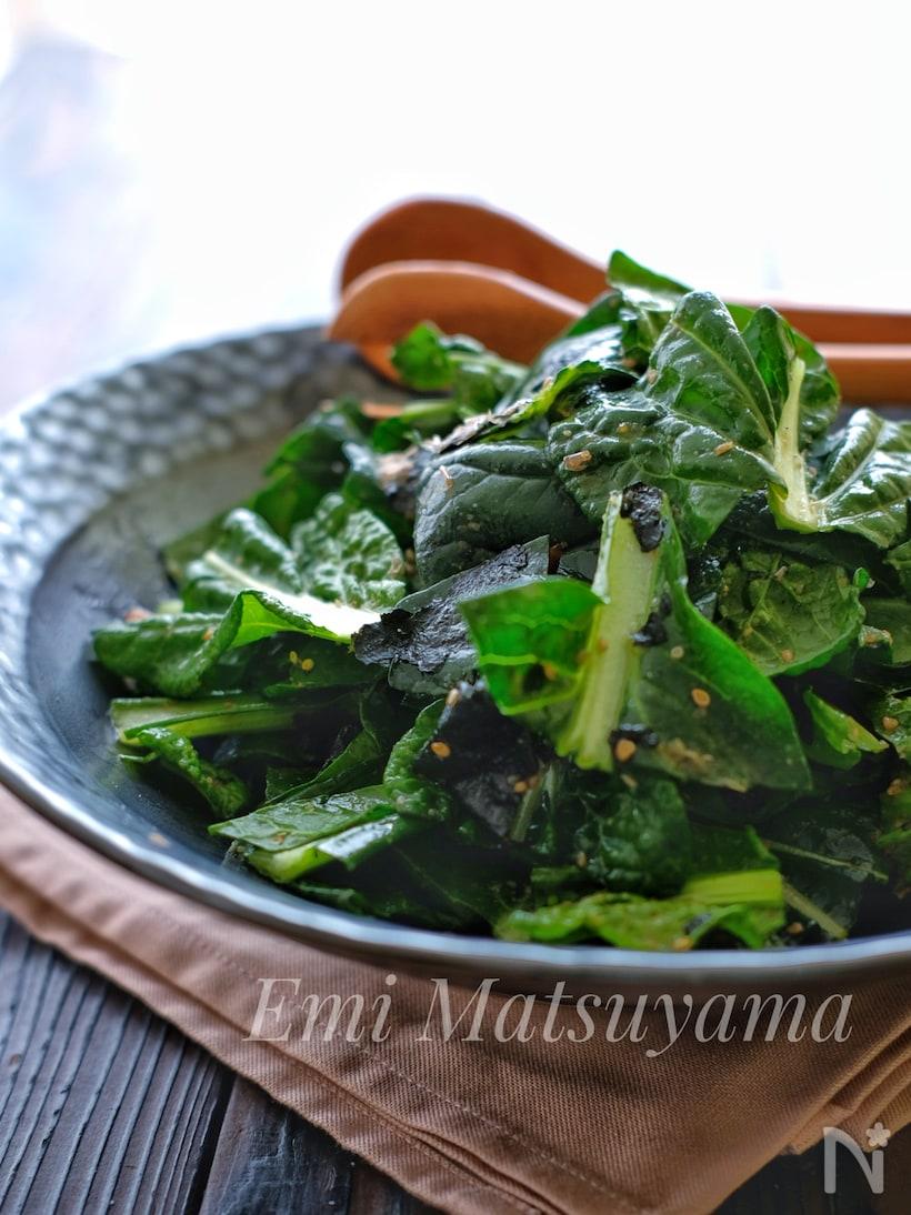 グレーの皿に盛られた生の小松菜の和風サラダ