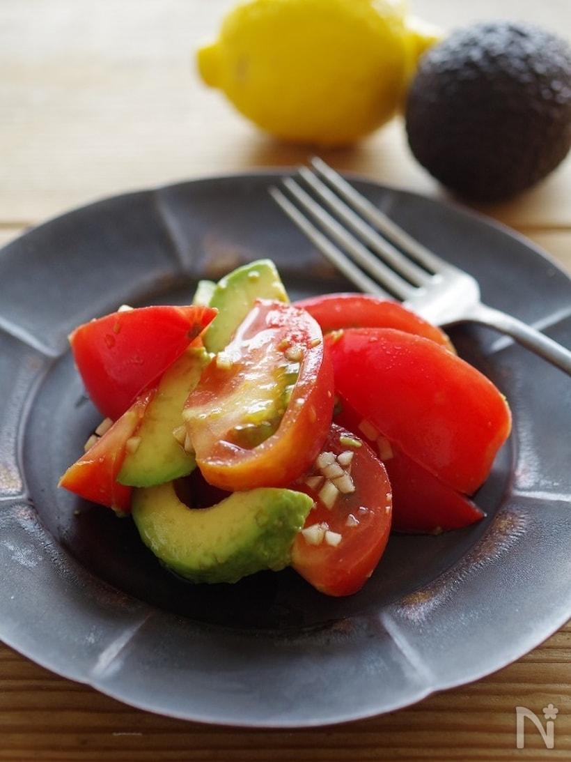 グレーの皿に盛られたアボカドとトマトのサラダ