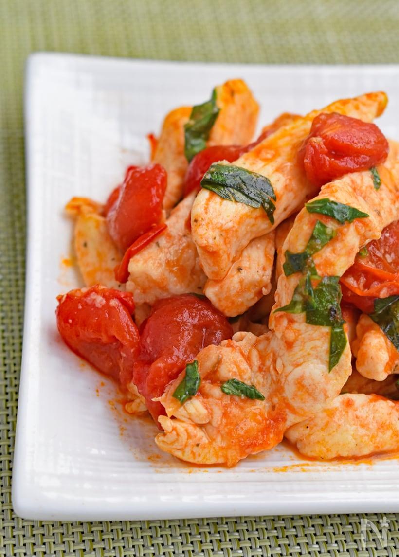 白い四角いプレートに盛り付けられたトマト、鶏肉、バジルの炒め物