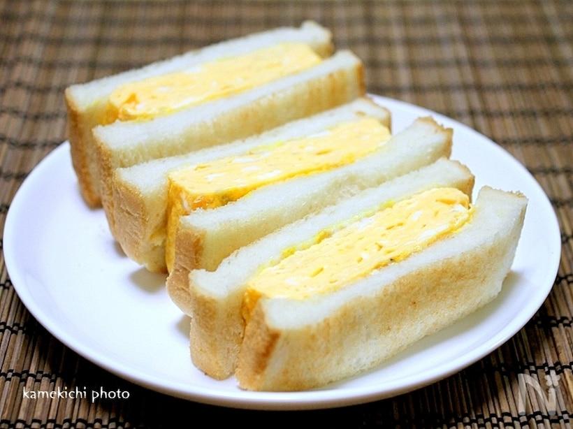 白の皿に盛られた卵焼きがサンドされたトースト