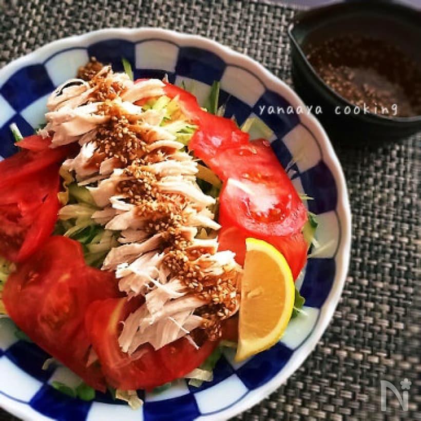 青い柄の丸皿に盛り付けたトマトスライスと、割いた蒸し鶏
