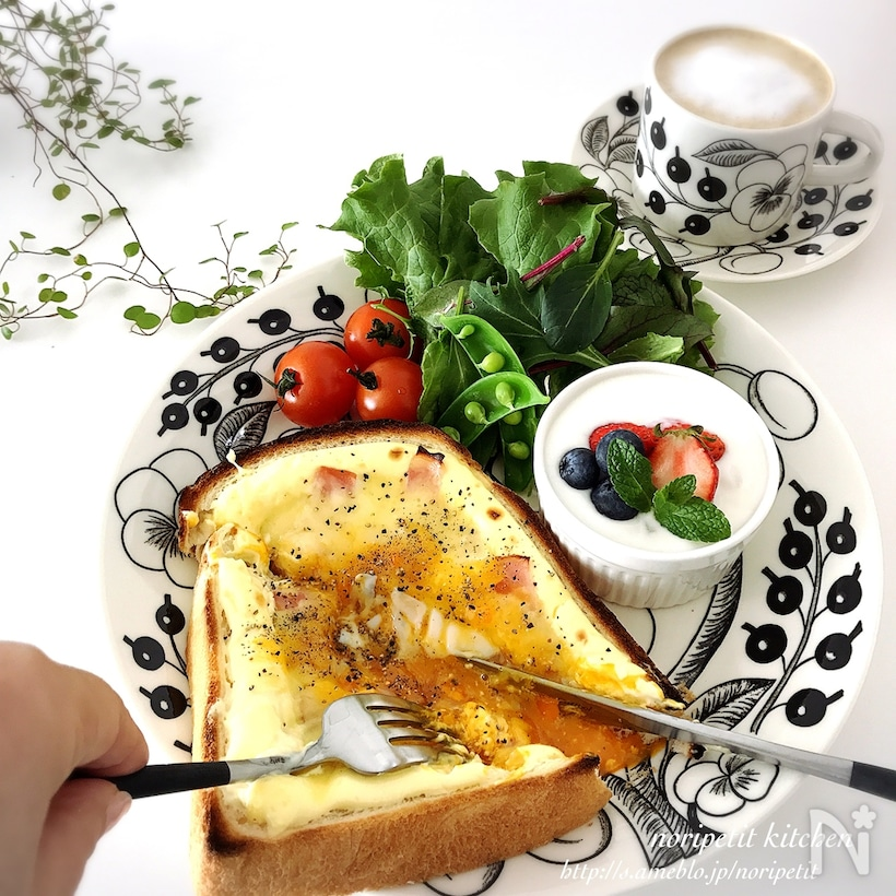 チーズや半熟たまごをのせたカルボナーラトーストをナイフとフォークで斜め半分に切っている最中の画像