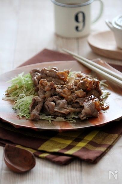 にんにく、バター醤油で炒めた豚肉を生の千切りキャベツと一緒にいただくひと品。