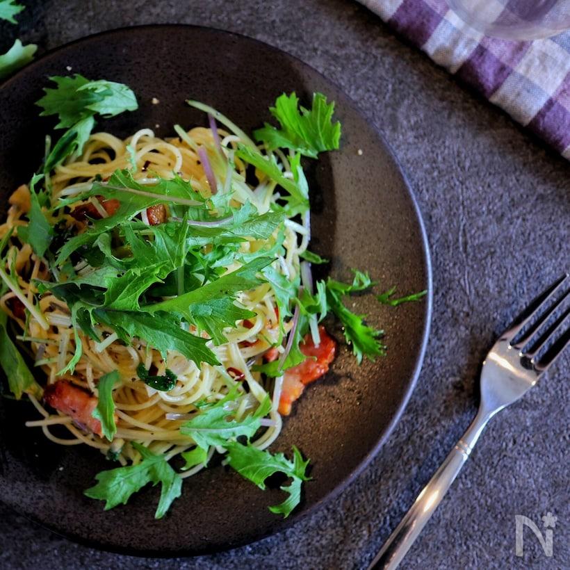 黒いお皿に盛られた水菜とベーコンのオイルパスタ