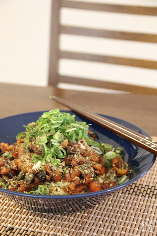 ネギがたっぷり盛られた汁なし担々麺が青の皿に盛られている