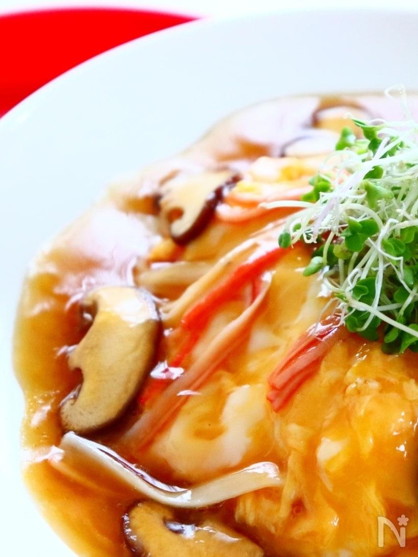 カニカマと椎茸が入った濃いめの甘酢餡をかけた天津飯のアップ画像