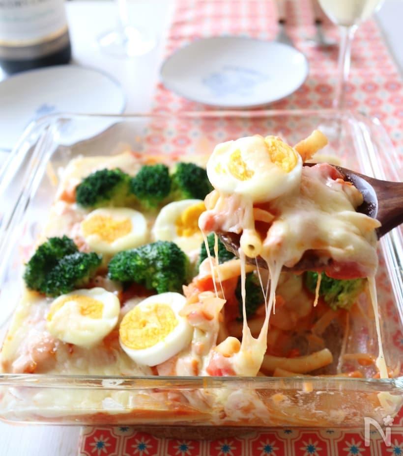 透明の耐熱容器に入ったサーモンのトマトクリームグラタンを木製のスプーンですくっている様子