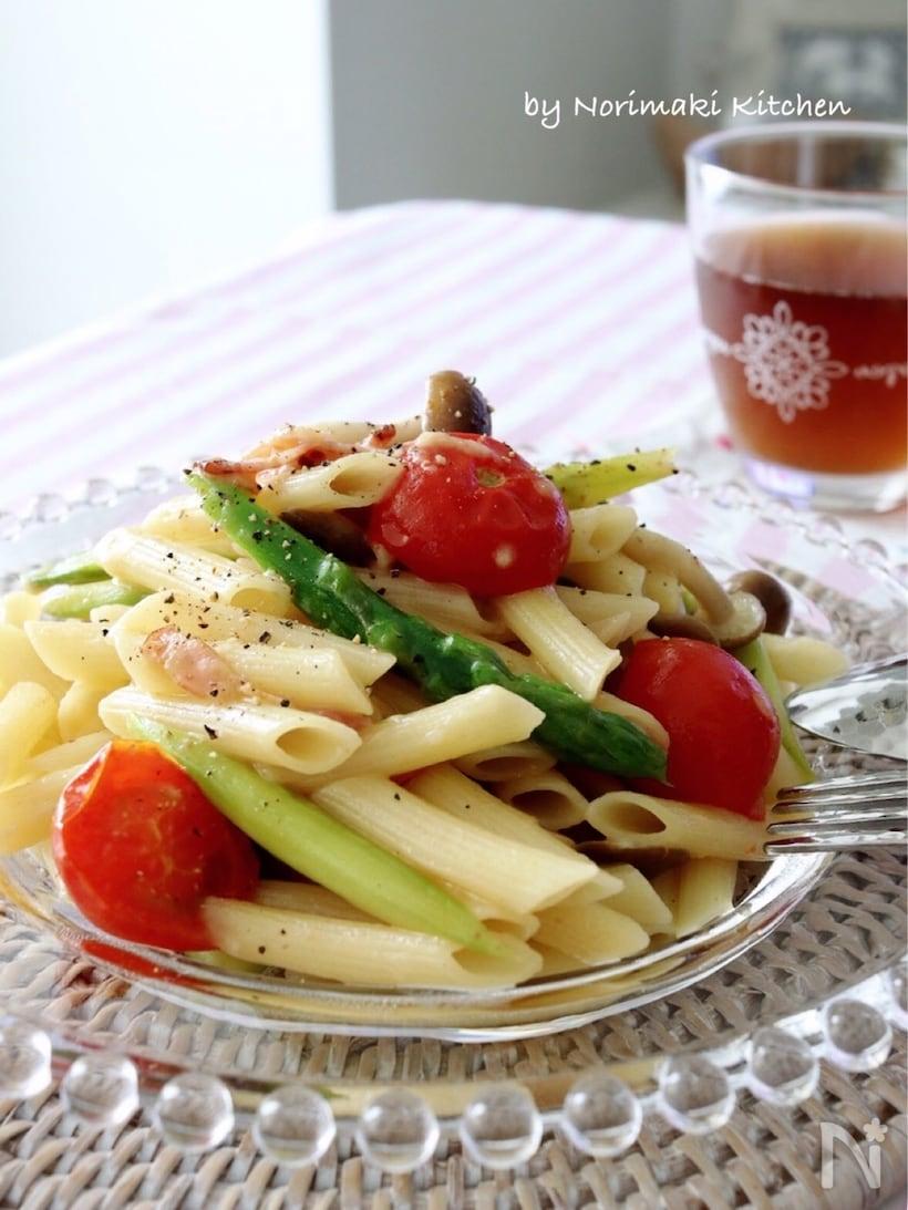 ガラスの皿に盛られたミニトマト、アスパラガスのペンネとグラスに入ったお茶