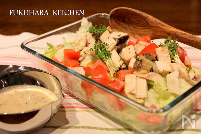 ガラスの四角いさらに入った鶏むね肉とレタスのシーザーサラダ