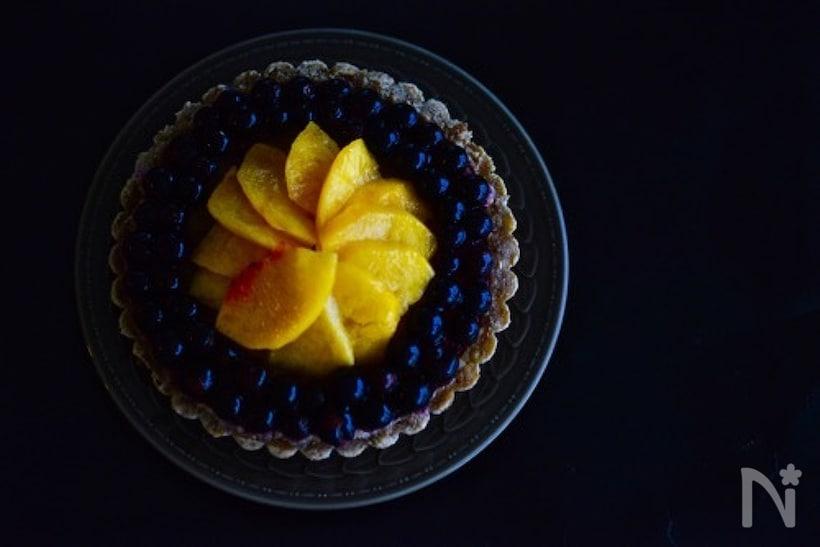 黒いお皿にのったブラックベリーと桃のジューシータルト